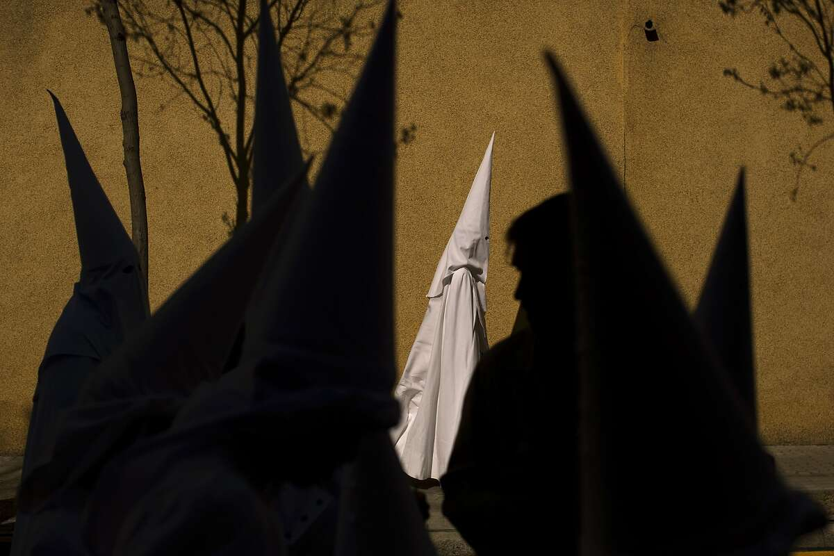 Hooded penitents from the La Paz brotherhood walk to the church to take part in a procession in Seville, Spain, Sunday, March 29, 2015. Hundreds of processions take place throughout Spain during the Easter Holy Week.