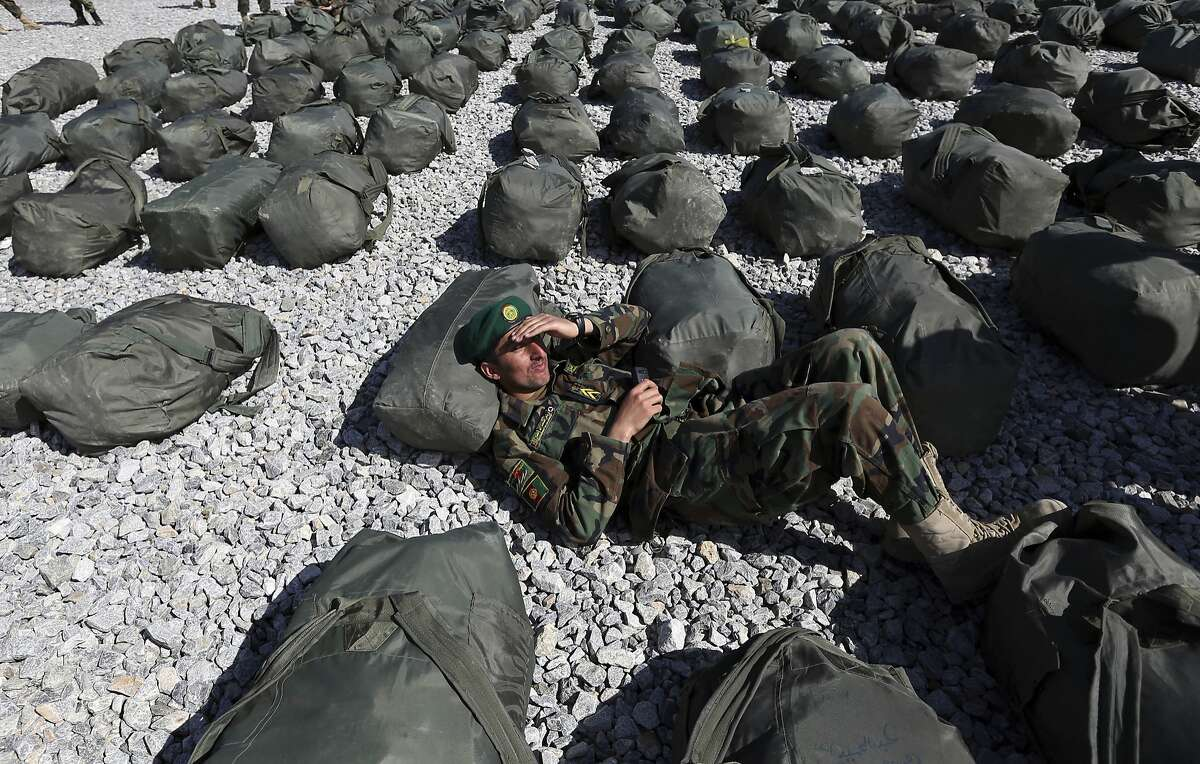 A new member of the Afghan National Army takes a rest after a graduation ceremony at the Afghan Military Academy in Kabul, Afghanistan, Sunday, March, 29, 2015. Over 2400 Afghan National Army (ANA) graduated after receiving a 4-month training program in Kabul.