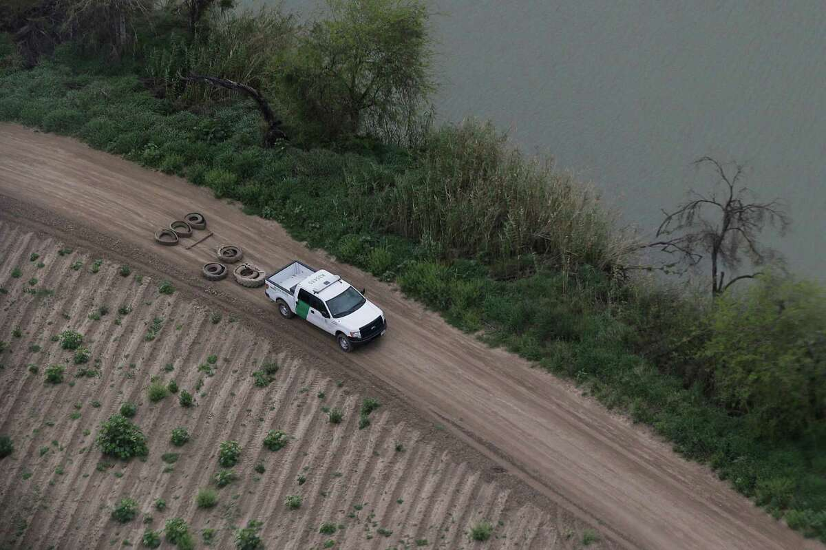 FILE - In this Feb. 24, 2015 file aerial photo, a U.S. Customs and Border Protection agent smooths a dirt road along the Rio Grande River on the Texas-Mexico border, near Rio Grande City, Texas. Drowning deaths have spiked since last fall as a surge of law enforcement along the Mexico border prompts immigrants, desperate to avoid detection by a surge of law enforcement, to choose more dangerous and remote crossings into South Texas. (AP Photo/Eric Gay, File)