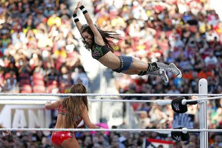AJ Lee soars throughs the air during her tag team win Paige over The Bella Twins during WrestleMania at Levi's Stadium in Santa Clara, Calif., on Sunday, March 29, 2015.