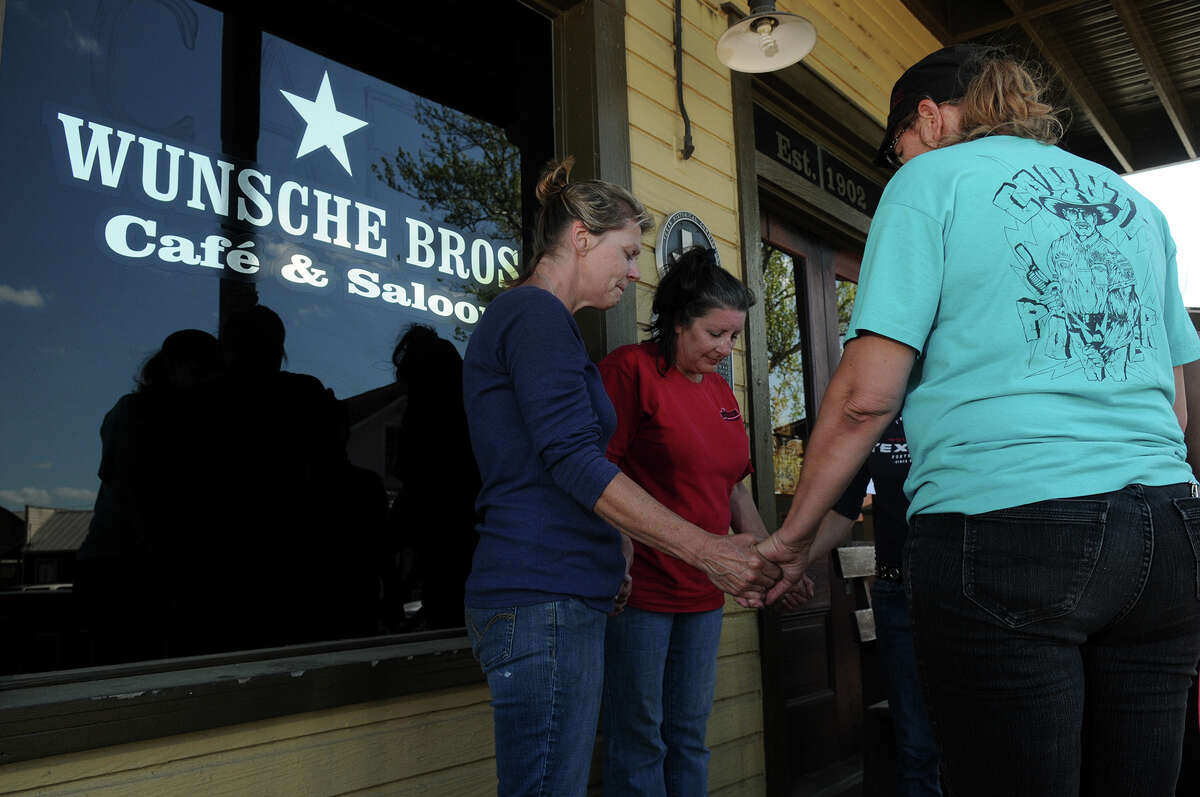Wunsche Bros. Cafe and Saloon employees, including Beth Vincent, from left, Kathleen O'Brien, Kim Mitchell, Debra Kelly, and former employee Sarah Herrera gather for a prayer Sunday afternoon at the front entrance to the restaurant in Old Town Spring which was damaged by fire early Sunday morning.