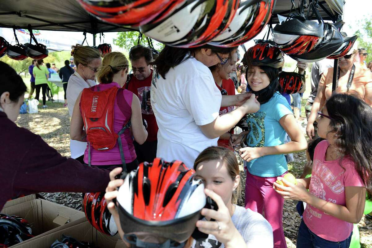 Faith Martinez, 12, is fitted for a free bicycle helmet by junior volunteer Sandra Vela at Síclovía. Three hundred and one free helmets were given out to kids under 18.