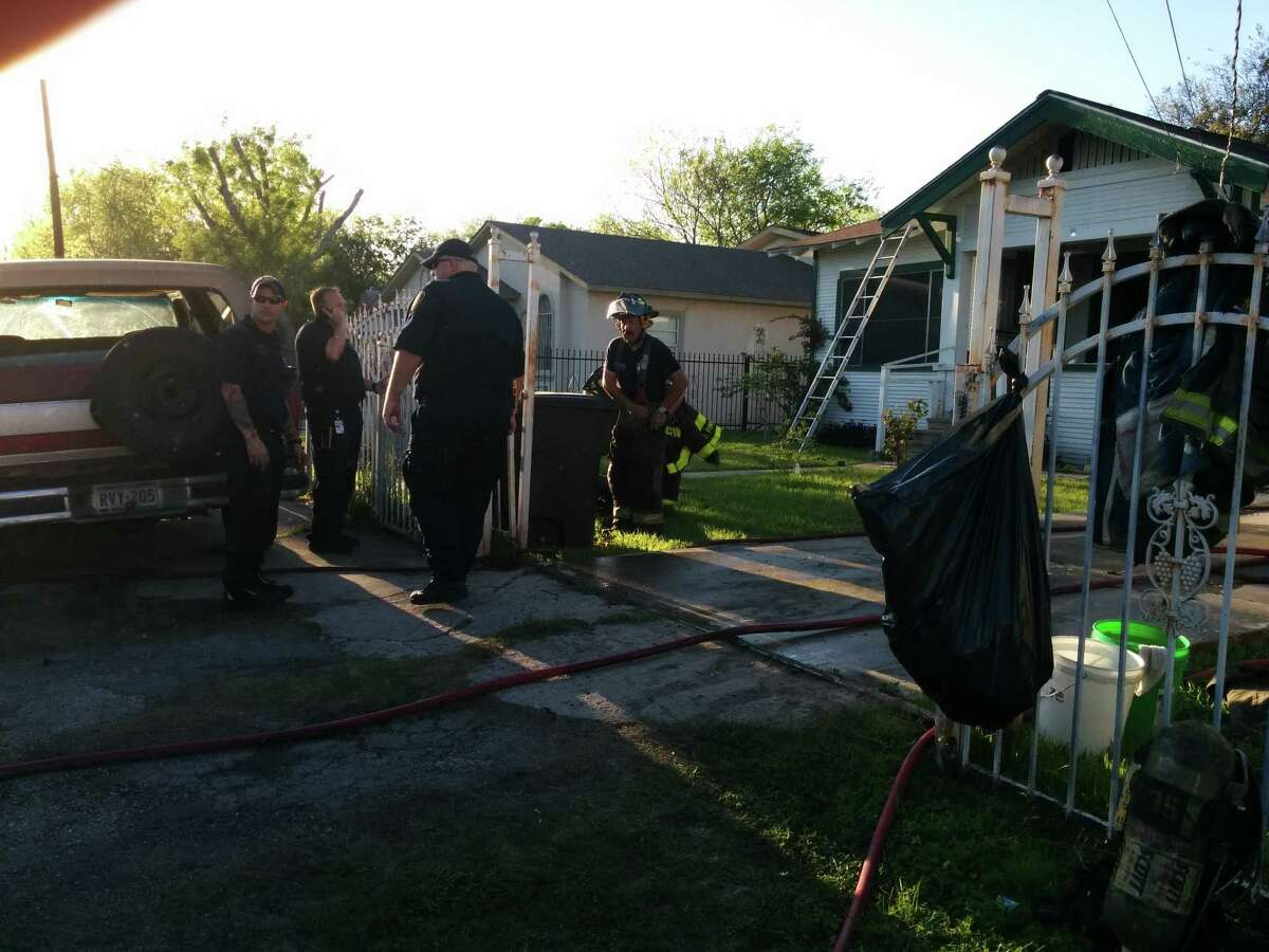 Fire fighters investigate the scene of a house fire on the 5000 block of Hemphill Drive.