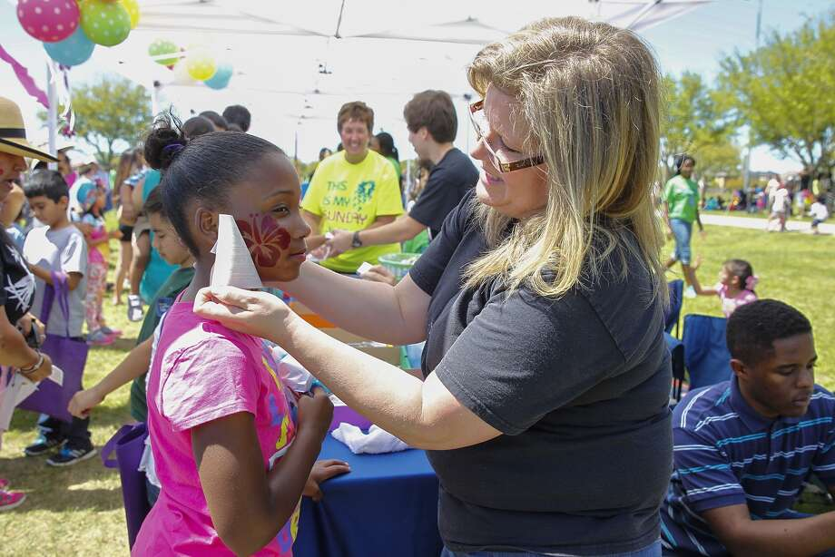 Jordan Lanthon, 10, gets a large tattoo on her face with the help of Debbie Miyahara during the 31st annual Eggstravaganza sponsored by the City Of Sugar Land at Eldridge Park on March 28, 2015. Photo: Diana L. Porter, For The Chronicle / © Diana L. Porter