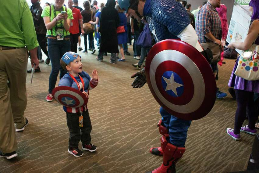 Shawn Raub, dressed as Captain America, is greeted by a larger version of himself during day two of Emerald City Comicon at the Washington State Convention Center on Saturday, March 28, 2015. The three day convention is the largest comic book and pop culture convention in the Pacific Northwest. The convention features cosplay, comic books, celebrities and more.