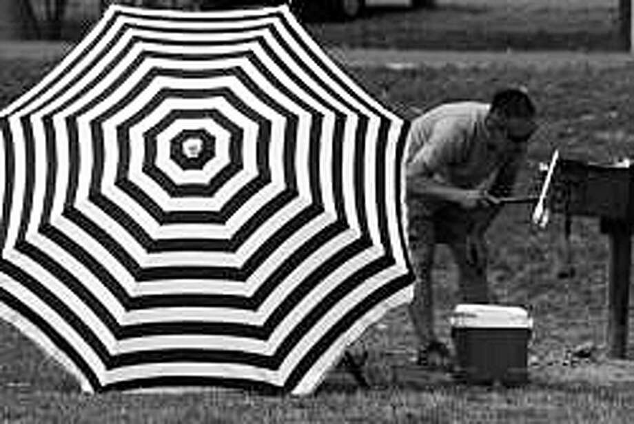 """Black and White Umbrella with Man Lighting Barbeque,"" one of the photographs by Larry Silver on display in the exhibit, ""Sherwood Island, 1975-2015,"" at the Westport Library. Photo: Contributed Photo / Westport News"