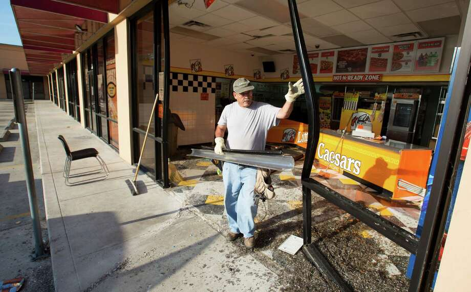 Crews clean up a Little Caesars after a car drove into it early Monday morning, March 30, 2015, in Houston. Photo: Cody Duty, Houston Chronicle / © 2015 Houston Chronicle