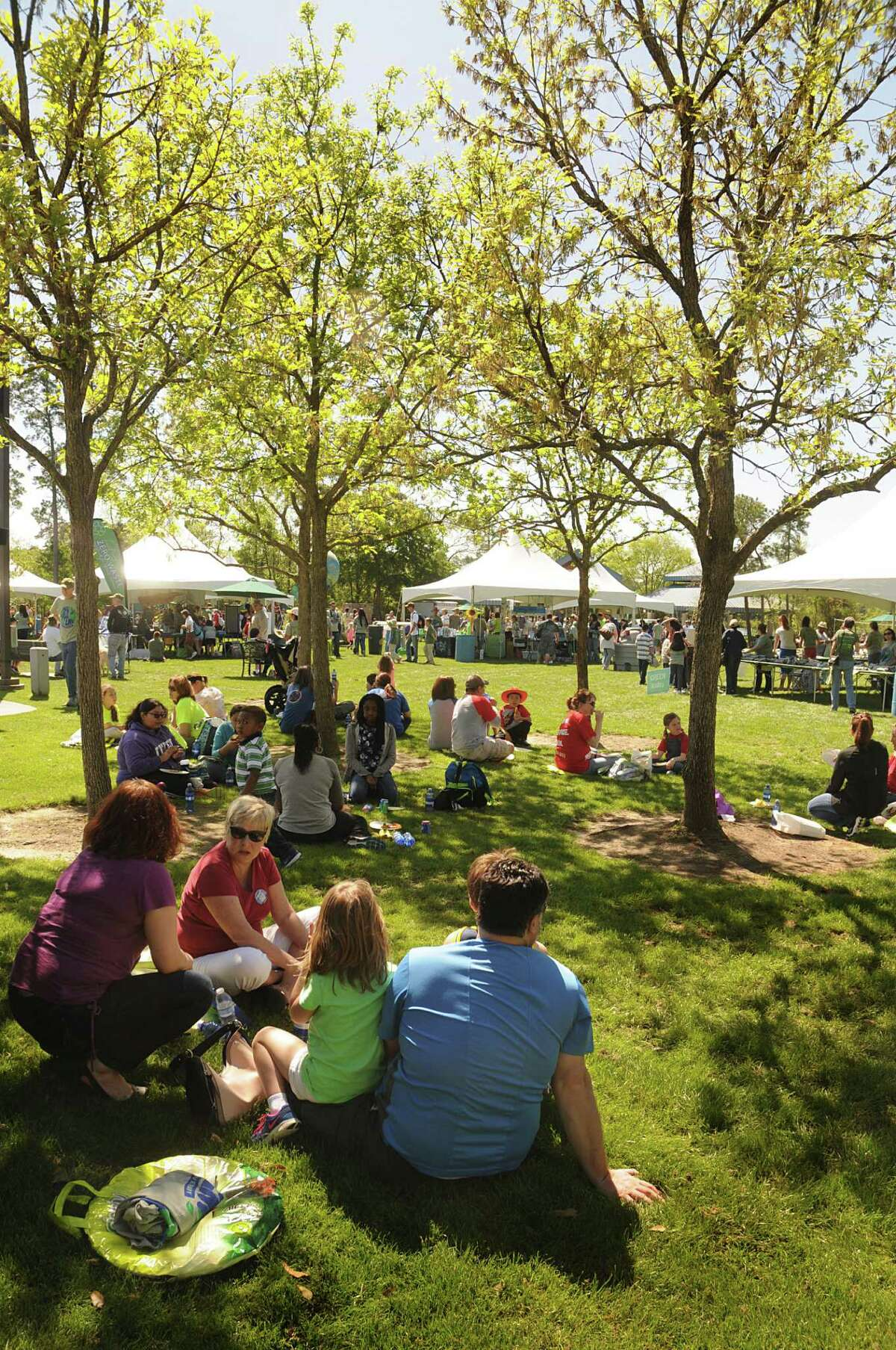 Guests enjoy the shade as they rest and eat during the Earth Day celebration at Northshore Park. Photograph by David Hopper