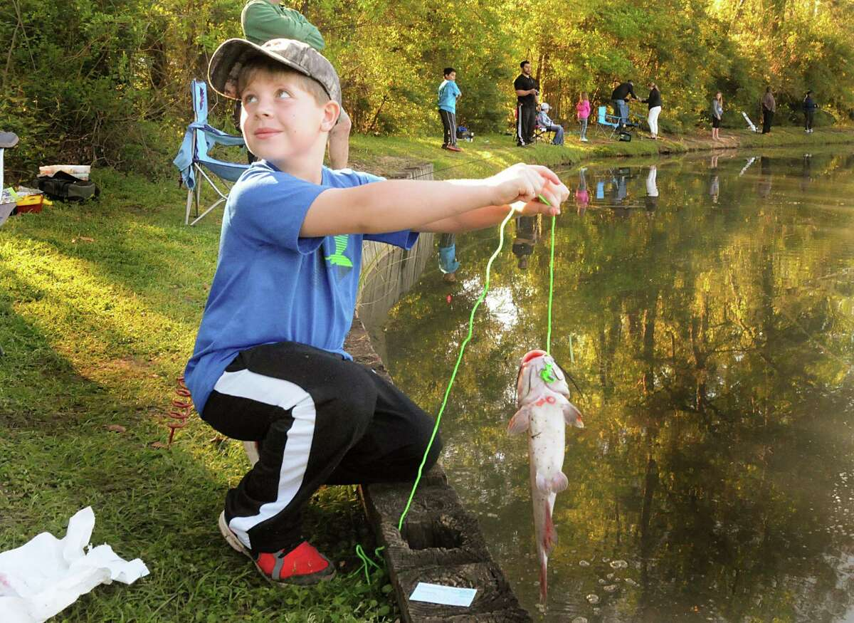 Grant Kitchens, of The Woodlands, shows off the big catfish he caught during the eighth annual Creekwood Fishing Derby, held at Creek Park Lake, 3383 South Panther Creek Drive.