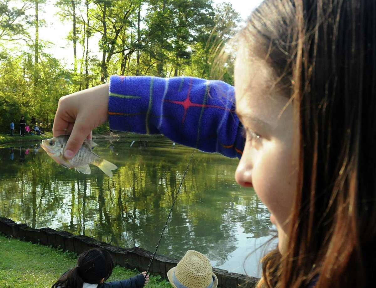 Autumn Curtis, of The Woodlands, holds the fish she caught that may have won the award for the smallest fish during the eighth annual Creekwood Fishing Derby, held at Creek Park Lake, 3383 South Panther Creek Drive.