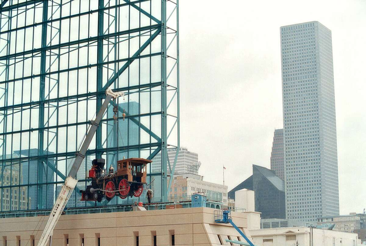 Construction workers lift a replica of a 19th century locomotive onto tracks that run alongside the moveable roof Enron Field, the Houston Astro's new downtown baseball stadium Saturday March 18, 2000, in Houston.