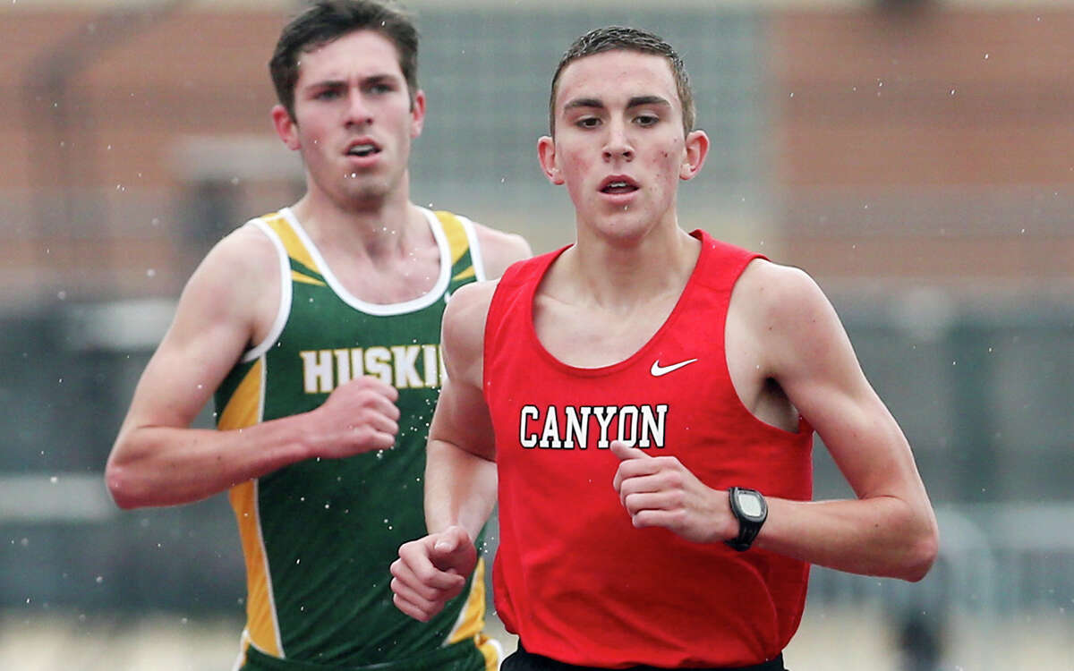 New Braunfels Canyon's Alex Rogers leads Holmes' Chris Myers as they approach the bell lap of the 3,200-meter run during Judson's Ron Faught Invitational at Rutledge Stadium on March 21, 2015. Rogers took first place in the event with a time of 9 minutes, 20.06 seconds. Myers finsihed second.