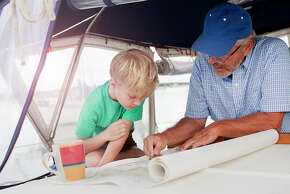 Boy and grandfather planning on navigation maps in sailboat cabin