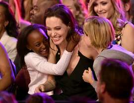 Actress Angelina Jolie hugs Zahara Marley Jolie-Pitt (L) and Shiloh Nouvel Jolie-Pitt (R) after winning award for Favorite Villain in 'Maleficent' during Nickelodeon's 28th Annual Kids' Choice Awards held at The Forum on March 28, 2015 in Inglewood, California.  (Photo by Kevin Winter/Getty Images)