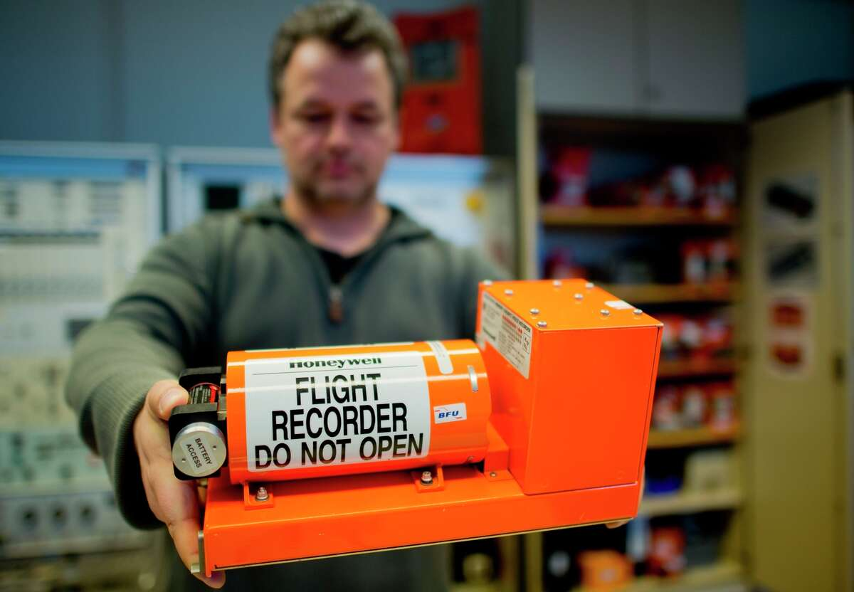 Officials at the crash site are still looking for a flight recorder like this one held by a German investigator.