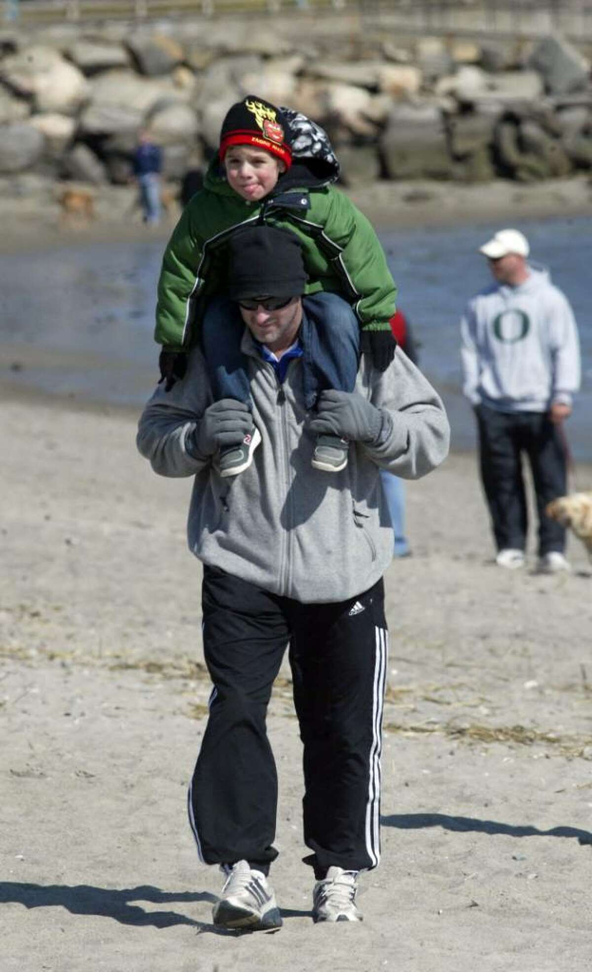 Ian Banner carries his son Hayen, 3, along Jennings Beach in Fairfield, Sunday, March 7, 2010. Hayden joined dozens of families, friends and pets walking along the beaches in the late winter sun.