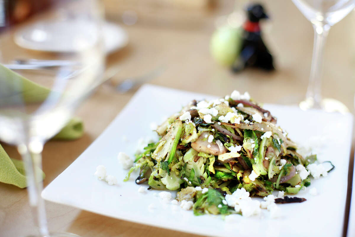 The warm Brussels sprouts salad comes with mushrooms, red onion, Valbreso feta and bacon vinaigrette at the Saw Shop.