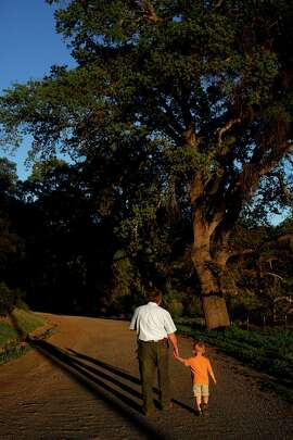 Kaj Ahlmann, owner of Six Sigma Ranch & Winery, walks with his grandson Caleb Ahlmann, 4, on his property in Lower Lake.