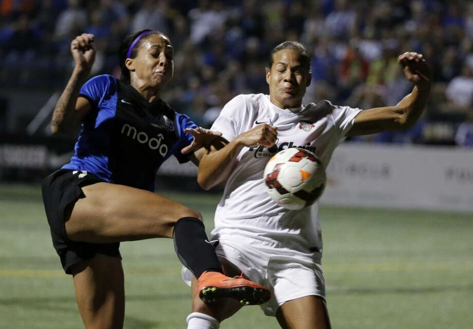 Seattle Reign FC's Sydney Leroux, left, and Washington Spirit's Toni Pressley collide in front of the Washington goal in the second half of a NWSL semifinal soccer match Sunday, Aug. 24, 2014, in Seattle. Washington was called for a foul on the play and Seattle scored on a penalty kick. The Reign won 2-1. (AP Photo/Elaine Thompson) Photo: AP