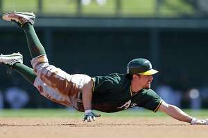 Oakland Athletics' Billy Burns dives back into second base after being tagged out by Colorado Rockies' Troy Tulowitzki in an attempted steal of second base in the first inning of a spring training exhibition baseball game Friday, March 20, 2015, in Scottsdale, Ariz. (AP Photo/Ben Margot)