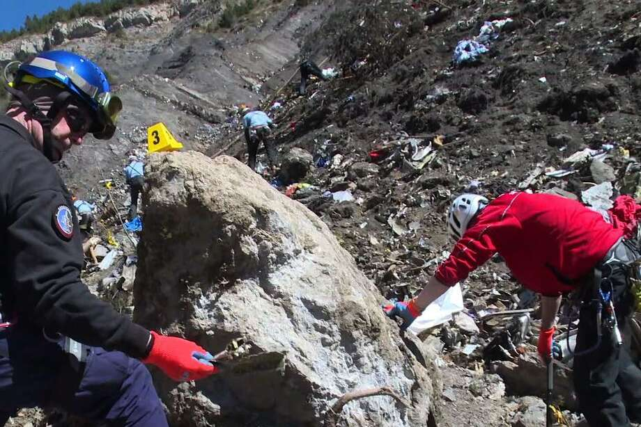 This screen grab taken from a handout video released by the French Interior Ministry on March 26, 2015 shows forensic experts of the French gendarmerie looking for the black box or clues on the site of the March 24 crash of a Germanwings Airbus A320 in which all 150 people on board were killed. AFP PHOTO / MINISTERE DE L'INTERIEUR RESTRICTED TO EDITORIAL USE - MANDATORY CREDIT AFP/MINISTERE DE L'INTERIEUR - NO MARKETING NO ADVERTISING CAMPAIGN - DISTRIBUTED AS A SERVICE TO CLIENTS-/AFP/Getty Images Photo: -, Handout / AFP / Getty Images / AFP