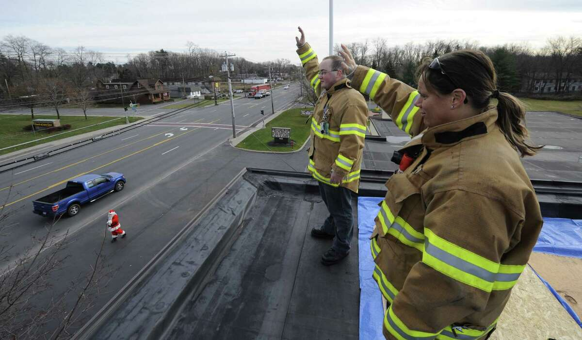 Assistant Chief of Department Meaghan Sammons, right, and Lt. James Burnetter wave to passing traffic from the roof of the Midway Fire House for their overnight stay to raise $5000 for local families Dec. 2, 2011, in Colonie, N.Y. (Skip Dickstein/Times Union archive)