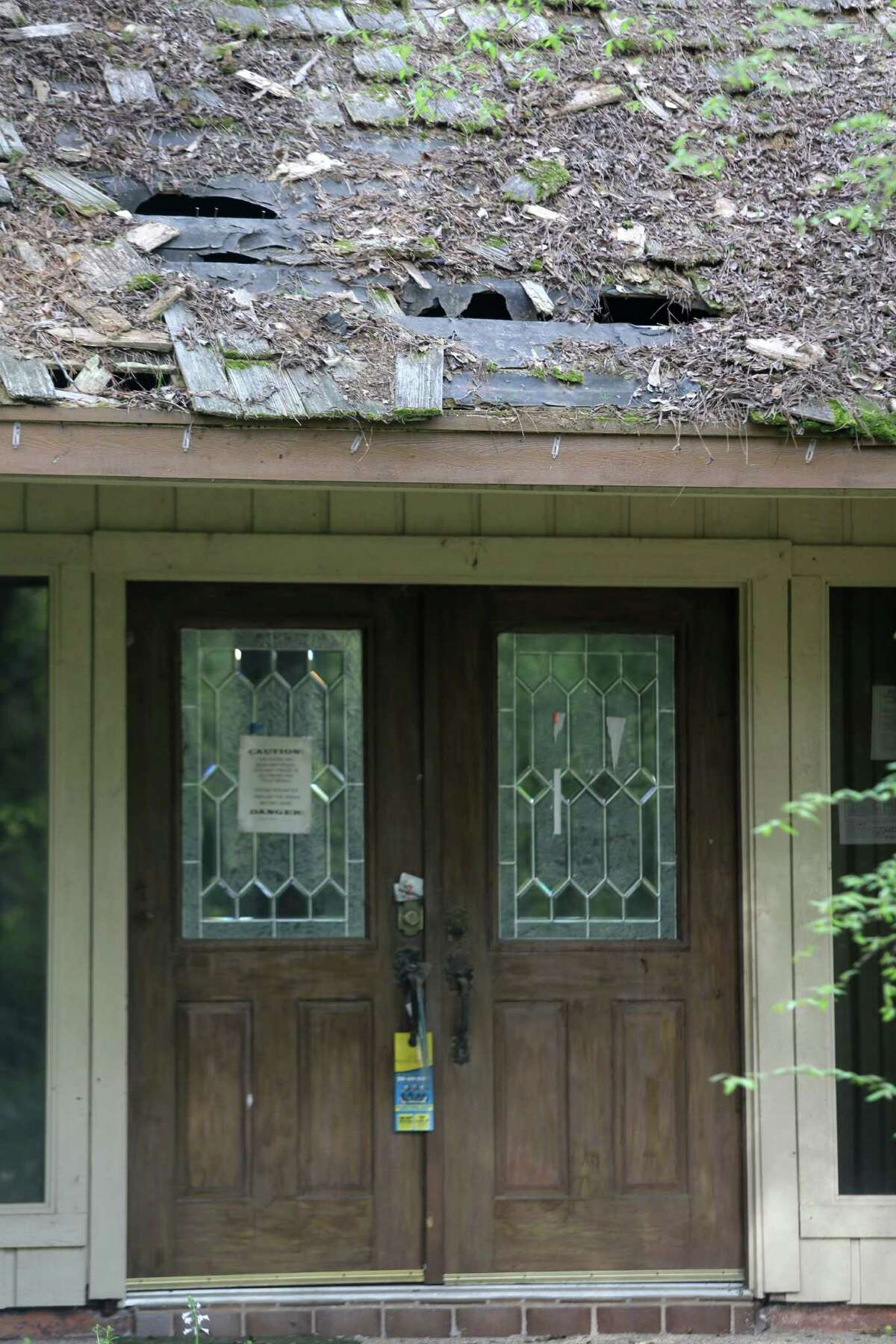 A view of holes in the roof over the front door of a house at 2014 S. Wildwind Circle in The Woodlands that was left to deteriorate over years is shown Wednesday, March 25, 2015. ( Melissa Phillip / Houston Chronicle )