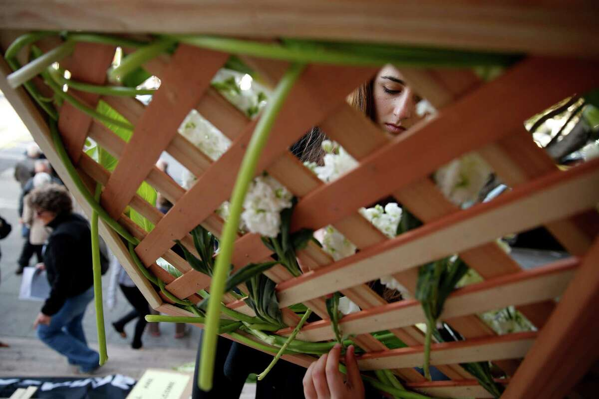 Caitlyn Cournale, 17, who has a sister who attends Sacred Heart Cathedral, helps prepare a flowered cross before joining other opponents of Archbishop Cordileone's new rules for teachers at Catholic high schools in a Holy Week procession from Mission Delores Church to St. Mary's Cathedral in San Francisco, Calif., on Monday, March 30, 2015.