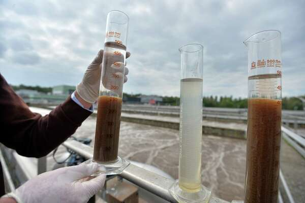 TO GO WITH AFP STORY Cedric SIMON Frederic Pierre, project manager at the waste-water treatment plant, in Strasbourg, eastern France, shows 3 containers, explaining the process how the city's waste-water (C) is changed into clear water and sludge (L); this sludge will finally be digested by bacterium and create biogas transformed into biomethane, on September 1, 2014. For the first time in France, the company will inject this biomethane into the natural gas network.    AFP PHOTO / PATRICK HERTZOG