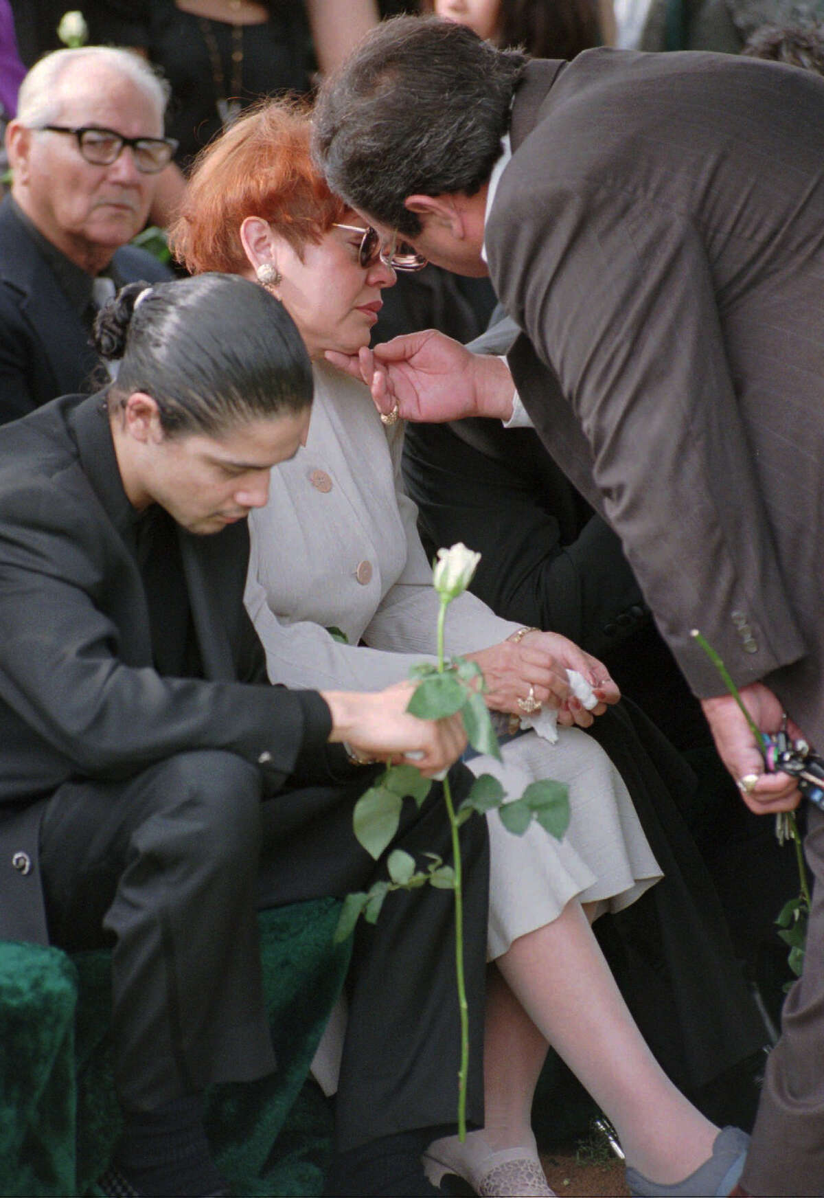 Father of slain Tejano music star, Abraham Quintanilla, right, consoles his wife, Marcella, as Chris Perez, husband of Selena, bows his head during funeral services Monday, April 3, 1995, in Corpus Christi, Texas. Selena was fatally shot Friday at a Corpus Christi motel. (AP Photo/David J. Phillip, Pool)
