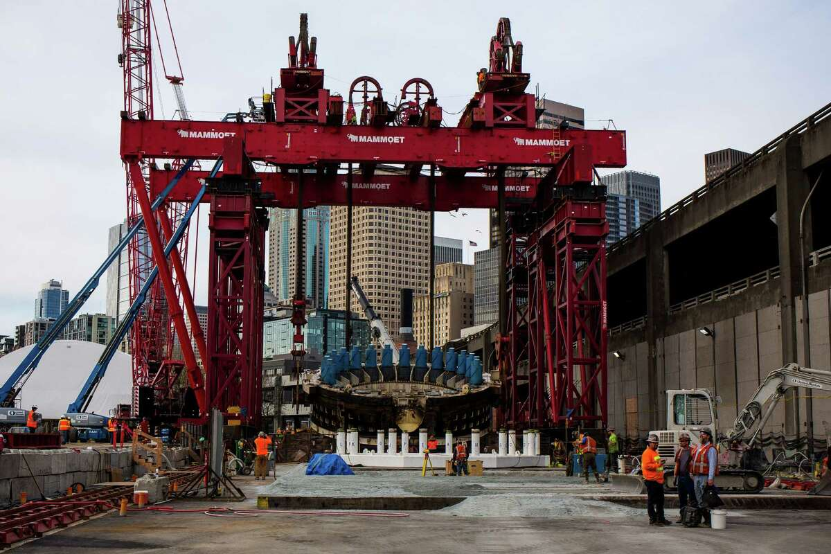 Bertha's 2,000-ton, 57.5-foot cutterhead and drive unit make the slow, 120-foot upward journey from the pit to street level for later repair, photographed Monday, March 30, 2015, in Seattle, Washington. As the front end of the machine cleared the access pit, the crane rotated the drill piece into a horizontal position to place it in a specially built cradle for later disassembly and repair. Previously, crews removed three pieces of Bertha's exterior from the pit, the largest weighing 270 tons.