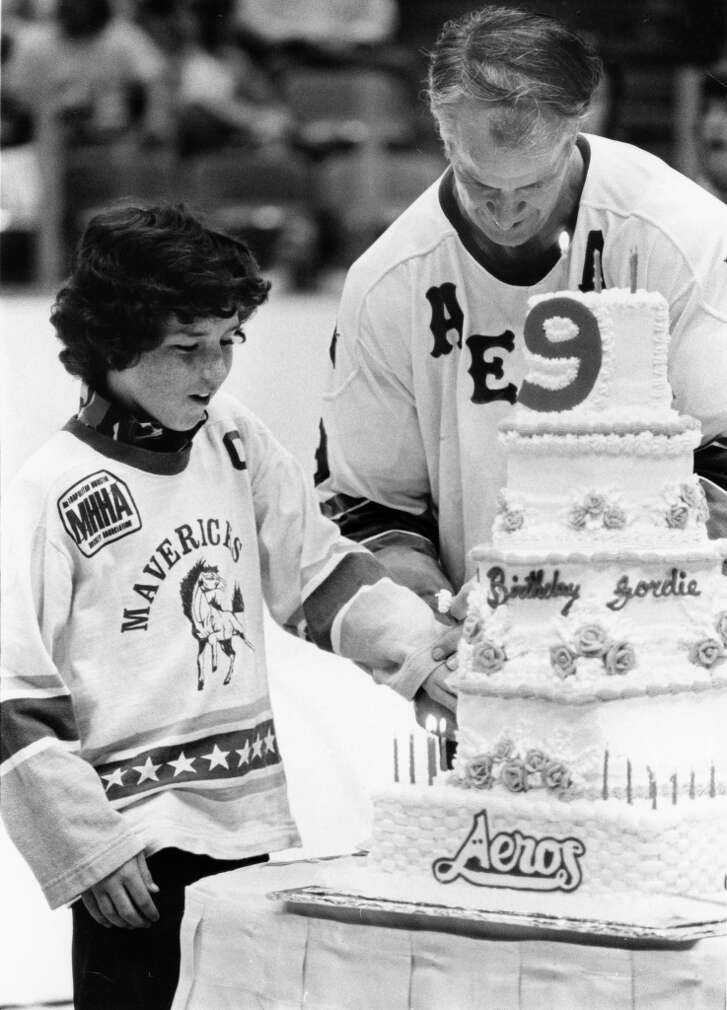 04/06/1976 - Kevin Dineen, left, son of Houston Aeros coach Bill Dineen, lends a helping hand to Gordie Howe during ceremonies between periods Tuesday night at The Summit. The crowd of 12,091 sang happy birthday to the 48-year-old star, who celebrated the event by scoring a goal and assisting on two others as the Aeros defeated Phoenix, 8-5, assuring the defending Avco World Trophy champions home-ice advantage in the upcoming World Hockey Association playoffs.