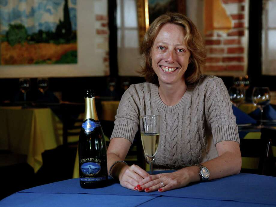Bistro Provence owner Genevieve Guy poses for a portrait with a glass of Cremant D'Alsace Domaine Charles Baur Brut Thursday, March 26, 2015, in Houston.  ( James Nielsen / Houston Chronicle ) Photo: James Nielsen, Staff / © 2015  Houston Chronicle