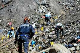 FILE - In this file photo dated Tuesday, March 24, 2015, provided by the French Interior Ministry, French emergency rescue services work at the site of the Germanwings jet that crashed on Tuesday, March 24, 2015 near Seyne-les-Alpes, France. The co-pilot of the Germanwings jet barricaded himself in the cockpit and intentionally rammed the plane full speed into the French Alps, ignoring the captain's frantic pounding on the door and the screams of terror from passengers, a prosecutor said Thursday.