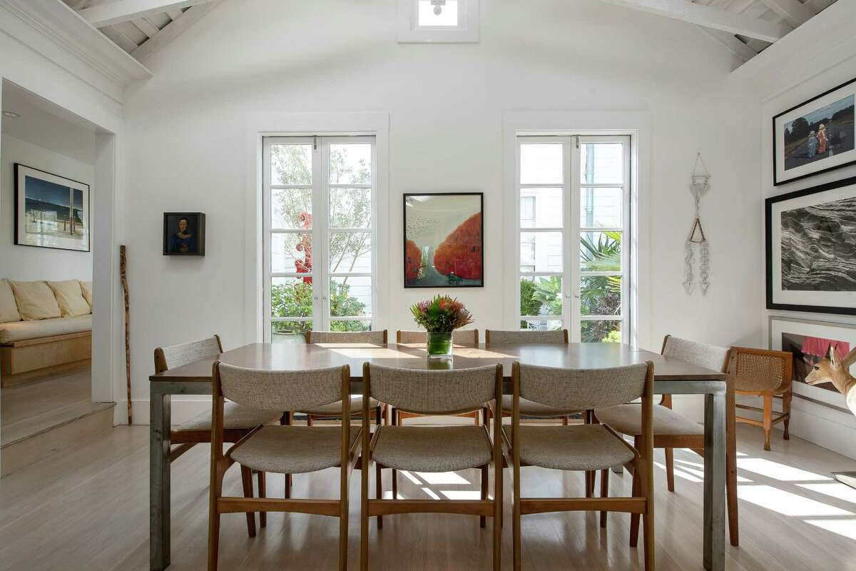 French doors with built-in glass panes, a skylight and a clerestory window bring natural light into the dining room.
