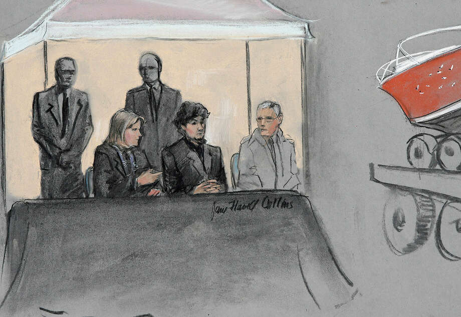A drawing from this month shows Dzhokhar Tsarnaev between his defense lawyers while the boat in which he was captured is displayed at his trial. Photo: Jane Flavell Collins / Associated Press / Jane Flavell Collins