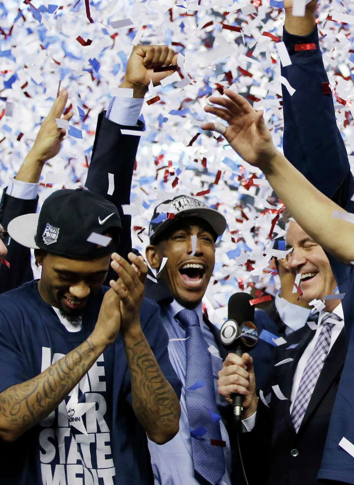 Connecticut head coach Kevin Ollie, center, celebrates with his team after their 60-54 victory over Kentucky in the NCAA Final Four tournament college basketball championship game Monday, April 7, 2014, in Arlington, Texas.