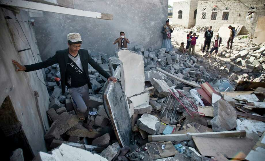 Yemeni residents gather near the rubble of houses destroyed by Saudi air strikes near the airport in the capital, Sanaa. Photo: Hani Mohammed / Associated Press / AP
