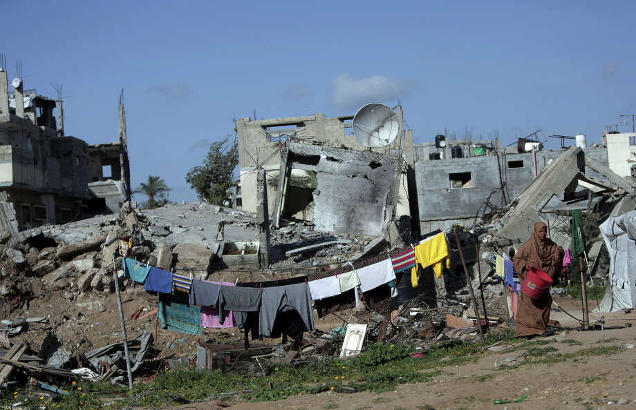 A Palestinian woman hangs clothes next to the rubble of her destroyed house in the Shijaiyah neighborhood of Gaza City. Many live in unsafe buildings while they wait for promised aid. Photo: Khalil Hamra / Associated Press / AP