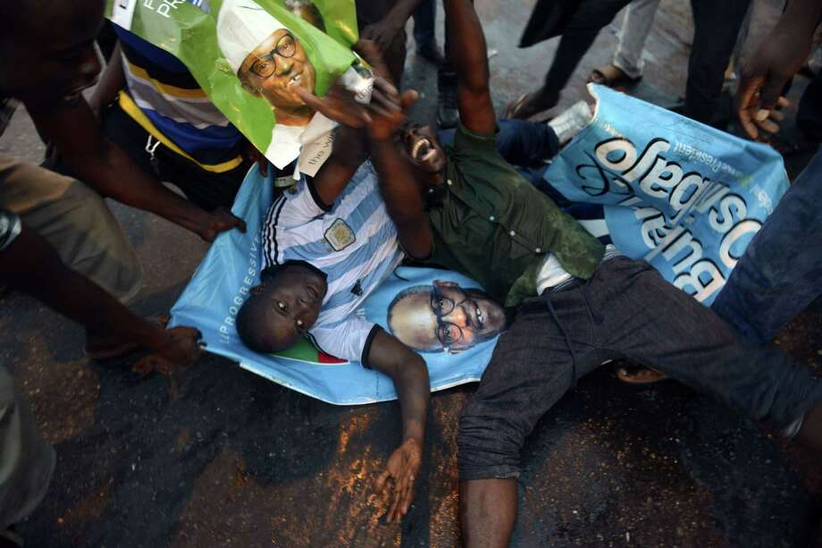 Two men lie on posters in Lagos to celebrate the victory of former military dictator Mohammadu Buhari over incumbent Goodluck Jonathan in the presidential election. Photo: PIUS UTOMI EKPEI / AFP / Getty Images / AFP