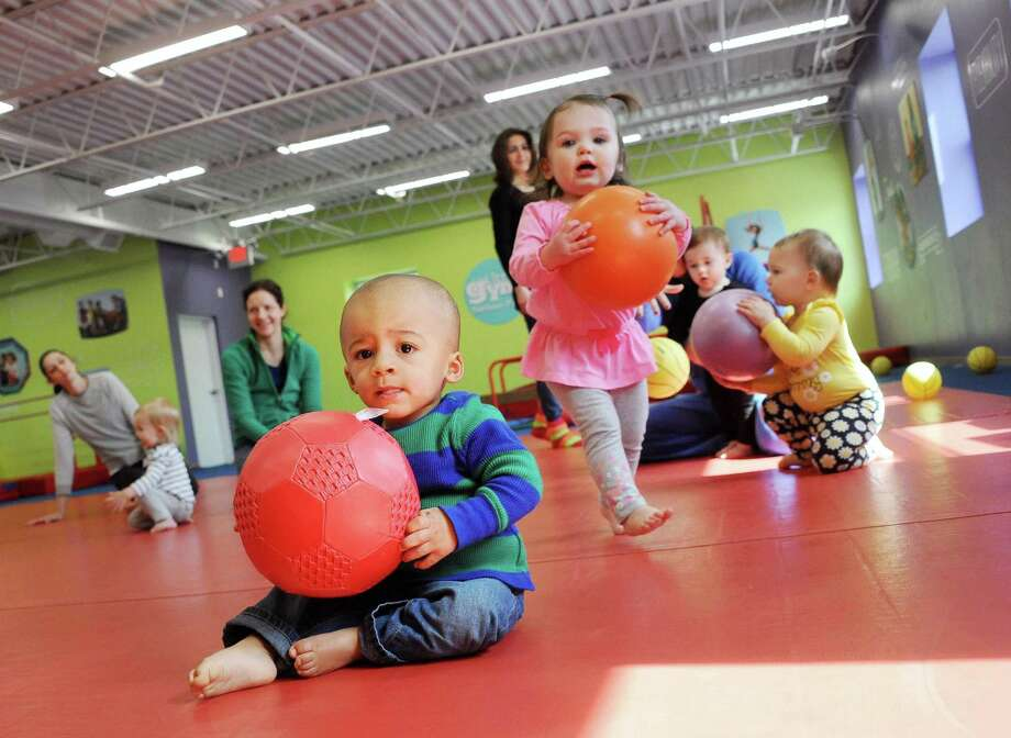13-month-old Isaiah Peters, left, of Troy and 16-month-old Emerson Lane of Loudonville during a class at The Little Gym Tuesday, March 24, 2015, in Colonie, N.Y. The Little Gym is just for kids (ages 4 months to 12 years) and focuses on everything from cognitive development to social skills to fitness.  (John Carl D'Annibale / Times Union) Photo: John Carl D'Annibale / 00031136A