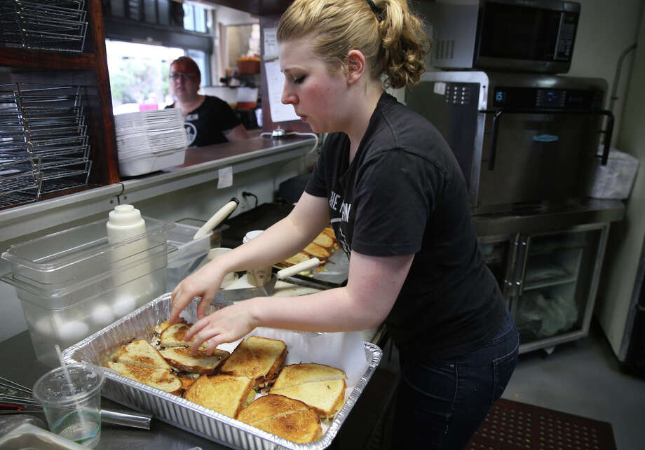 Summer Prueitt prepares sandwiches at the American Grilled Cheese Kitchen in San Francisco. Bills in the Assembly and state Senate would allow entrepreneurs to raise money by crowdfunding. Photo: Paul Chinn / The Chronicle / ONLINE_YES