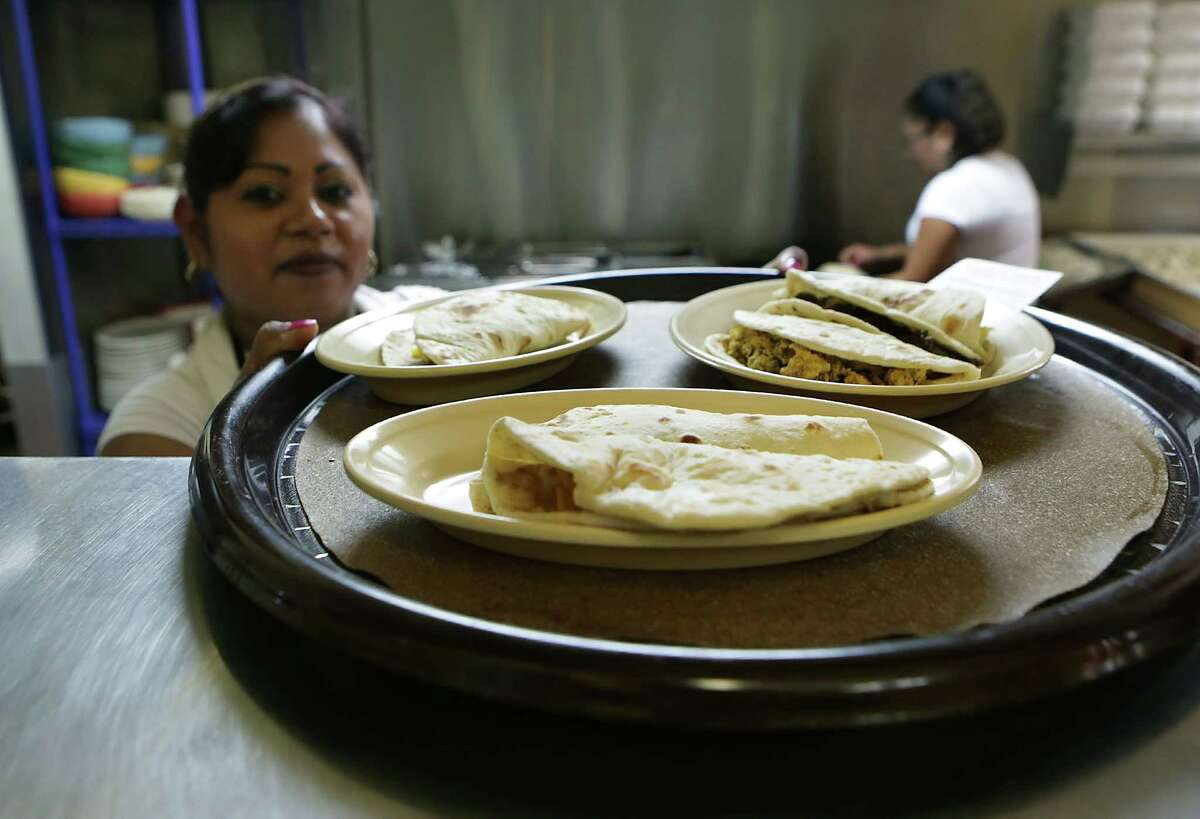 Rosa's Tacos To Go really brings it with the chicharron taco. Here, Esmeralda Ruiz puts up a finished order of tacos.