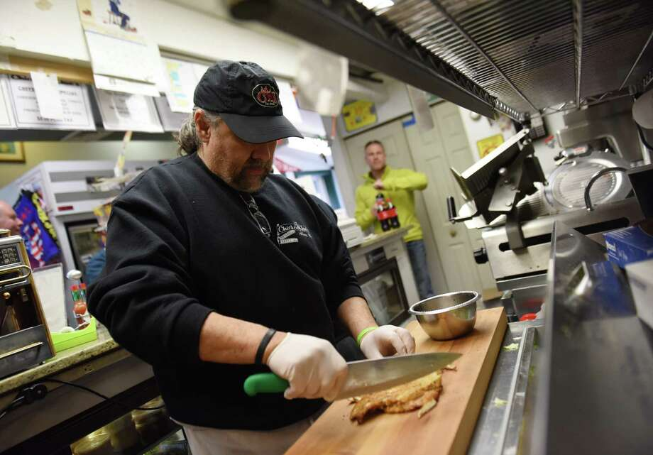 Owner Joe marini cuts a chicken cutlet to put on a wrap at Chicken Joe's in the Cos Cob section of Greenwich, Conn. Tuesday, March 31, 2015.  Greenwich High School students have launched a petition to add offerings from the popular lunchtime destination Chicken Joe's to the school lunch menu. Photo: Tyler Sizemore / Greenwich Time