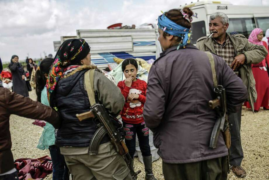 Displaced Syrians meet Kurdish fighters after Islamic militants were driven from town of Kobani. Photo: YASIN AKGUL / AFP / Getty Images / Yasin AKGUL