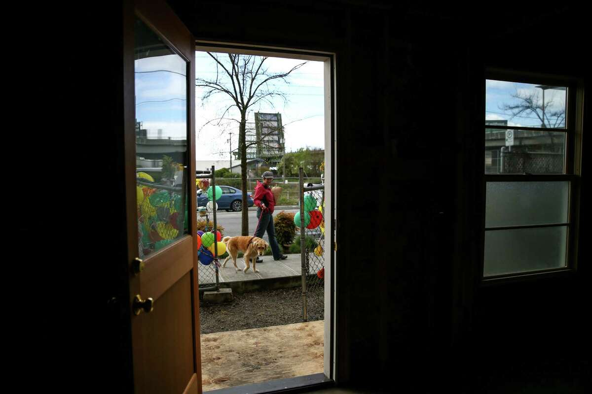 A dog is walked past the former home of Edith Macefield. The house went up for sale on March 31, 2015 in Seattle's Ballard neighborhood.