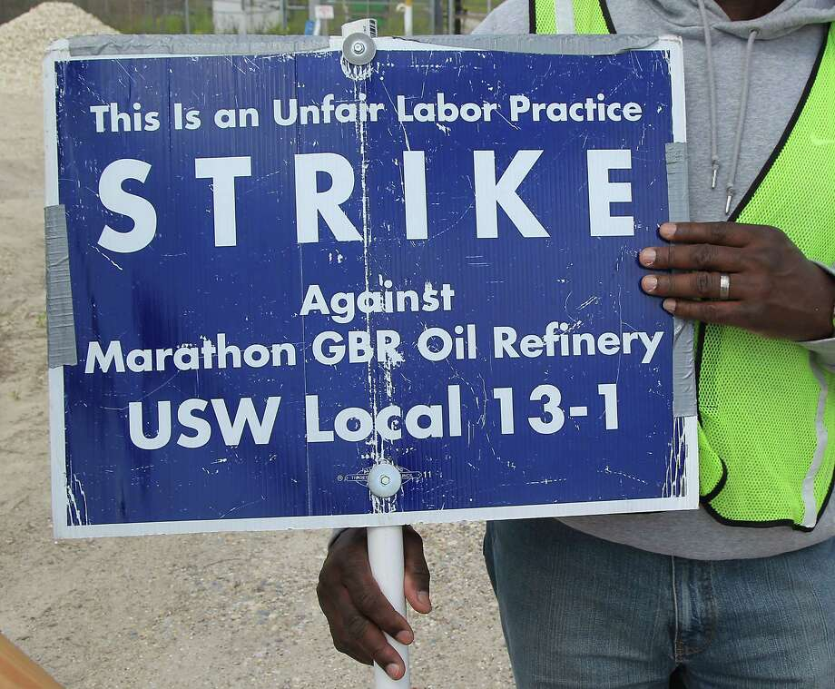 A United Steelworkers Local 13-1 union member displays a sign last month on a picket line. Photo: James Nielsen, Staff / © 2015  Houston Chronicle