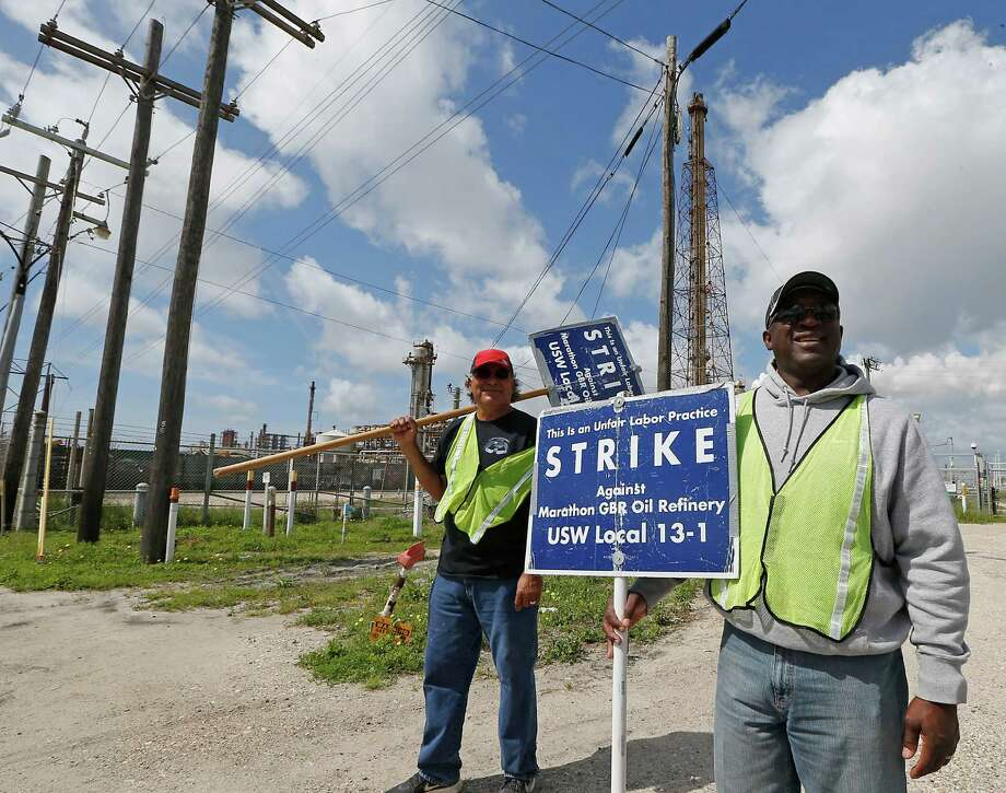 United Steelworker Local 13-1 union members Alex Medrano left, and Kent Davis right, carry signs on a picket line at Marathon Petroleum Company's Galveston Bay Refining Division plant Tuesday, March 31, 2015, in Texas City.  ( James Nielsen / Houston Chronicle ) Photo: James Nielsen, Staff / © 2015  Houston Chronicle