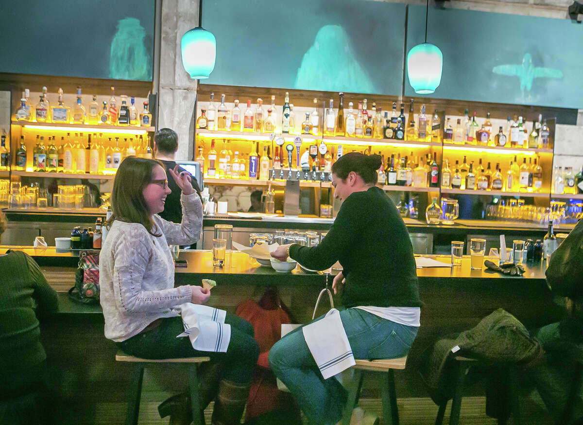 Diners enjoy cocktails during happy hour in the front bar at Comal in Berkeley, where the roast turkey is king all year long and the salsas are among the best around.