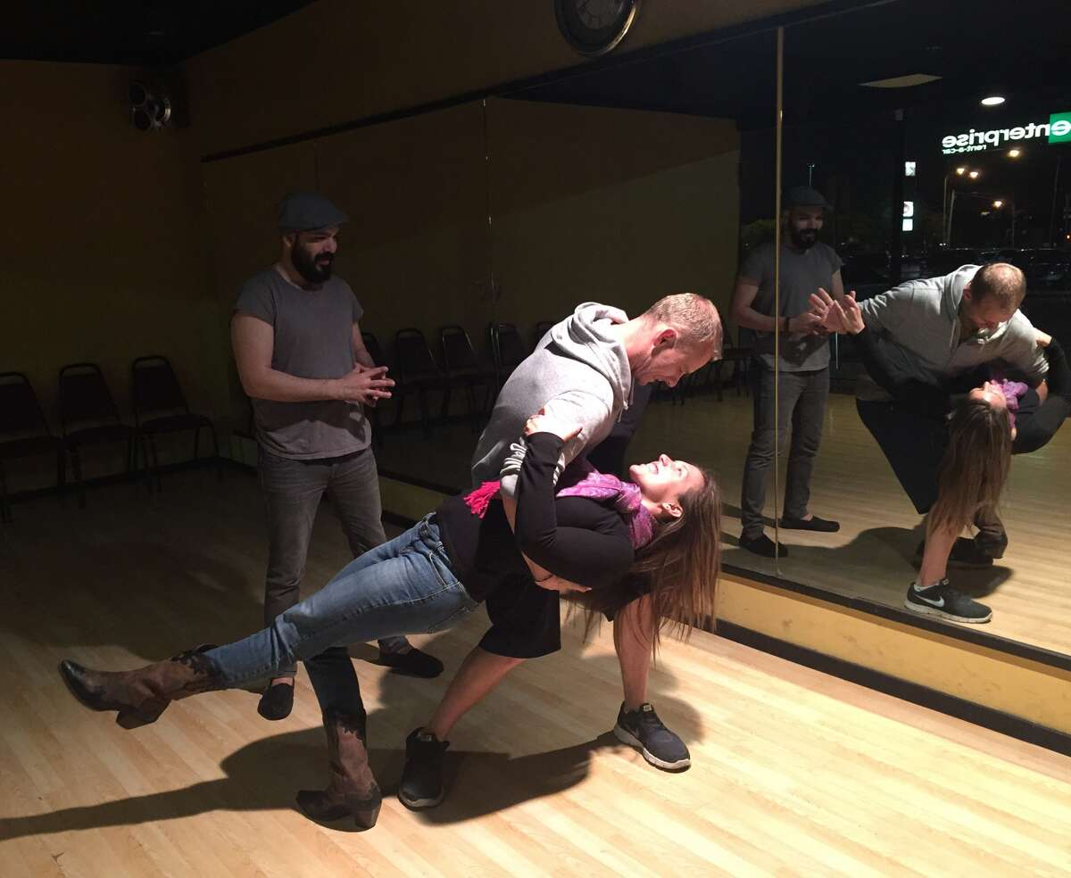 Chris Fahey, a new transplant to Houston, practices salsa dancing with his girlfriend.